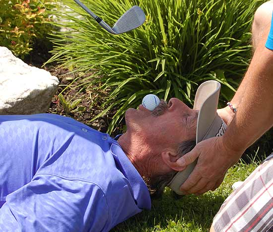 Kevin Turcotte lying on the grass with a golf ball in his mouth