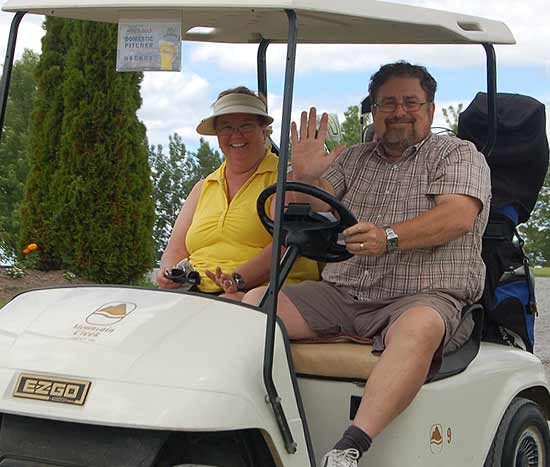 Nancy Paquette and hubb in a golf cart