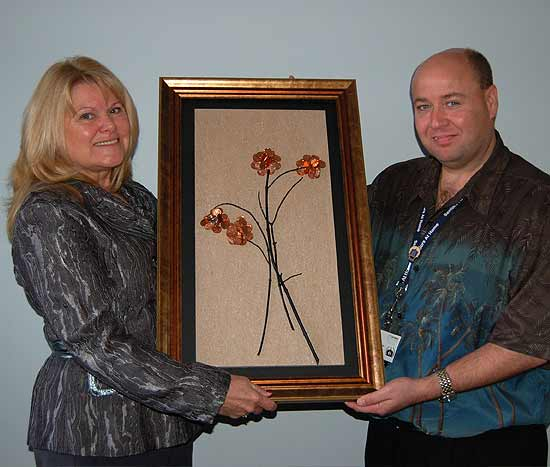 Volunteer Phyllis Doherty-Hereford presents her artwork to Dennis Harrington for the dedication of 'The Penny Time Room'