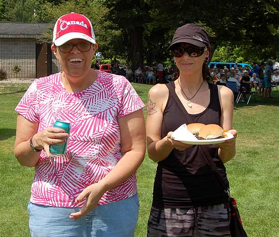 Tanya Rath carries a plate for a guest at the BBQ